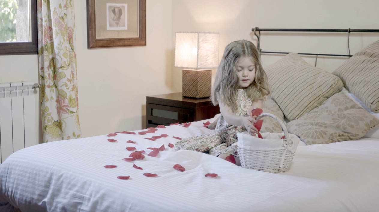 Niña con pétalos en habitación de Ribera del Corneja